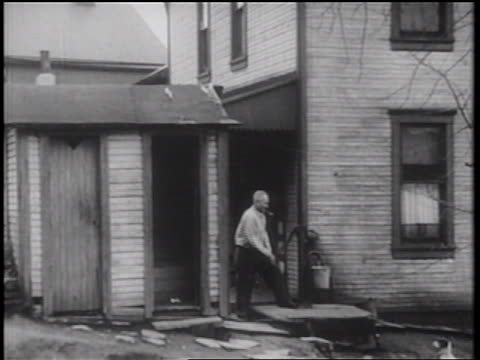 B/W 1939 man standing by house pumping water while smoking pipe / documentary