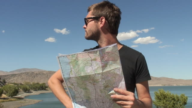 vidéos et rushes de ms, man standing by lake, looking at map, california, usa - regarder autour de soi