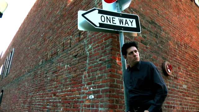 Man standing by one way sign