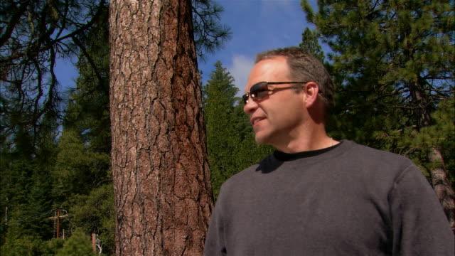 ms portrait man standing in forest + removing sunglasses/ fresno county, california - endast en medelålders man bildbanksvideor och videomaterial från bakom kulisserna