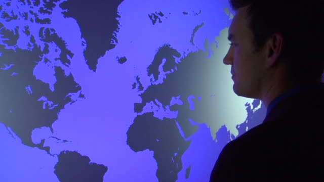 cu, ds, man standing in front of  blue world map - in front of stock videos & royalty-free footage