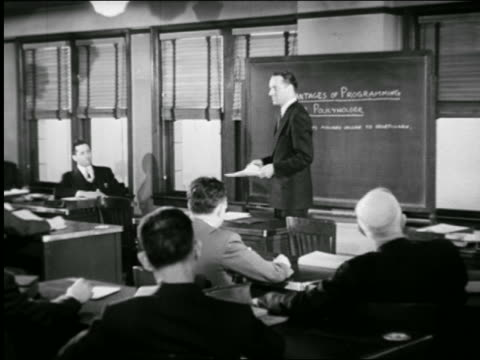 b/w 1947 man standing in front of chalkboard lecturing men at desks / industrial - b rolle stock-videos und b-roll-filmmaterial