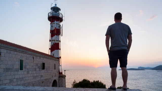 WS man standing in front of lighthouse overlooking the mediterranean sea at sunset
