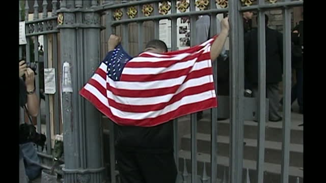man standing in front of trinity church in new york city and holding onto the railings with his head bowed and draped in the us flag; 2002. - 2000s style stock videos & royalty-free footage