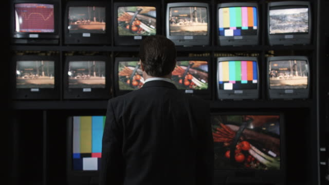 ms man standing in front of tv monitors, watching footage, dallas, texas, usa - guardare la tv video stock e b–roll