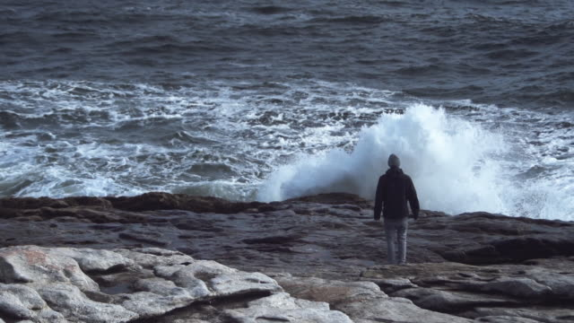 man standing in front of wave crashing on the shore of popham beach in maine, usa - maine stock videos & royalty-free footage