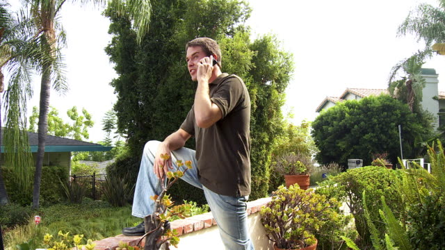 ms zi man standing in garden using mobile phone / sherman oaks, california, usa.   - see other clips from this shoot 1655 stock videos & royalty-free footage