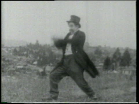 stockvideo's en b-roll-footage met b/w 1915 man standing in grassy field throwing cannon ball at someone offscreen / feature - 1915
