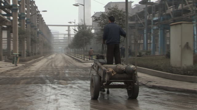 WS Man standing in horse drawn cart with two canisters as horse pulls cart down street/ Dongguan, China