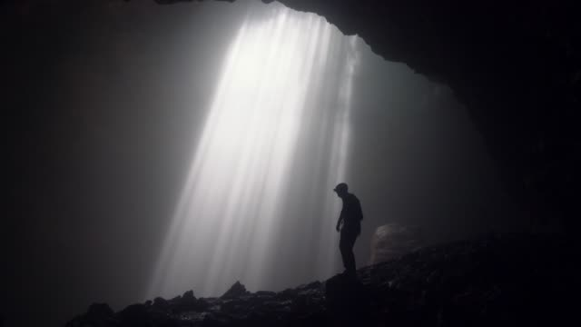 man standing in jomblan cave in sunbeams - stand stock videos & royalty-free footage