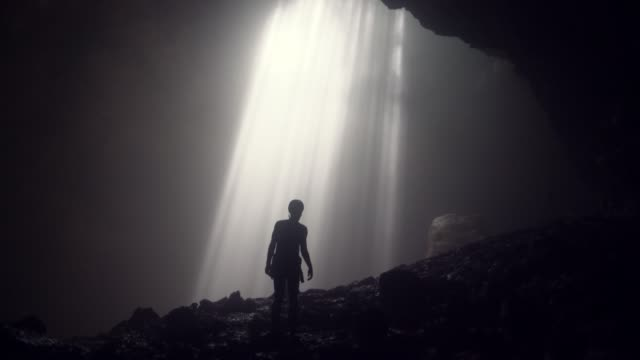 man standing in jomblan cave in sunbeams - esplorazione video stock e b–roll