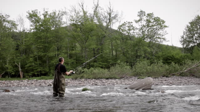 WS PAN Man standing in river fishing with full fishing gear / Woodstock, New York, USA