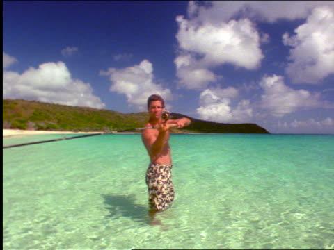 man standing in shallow ocean water casting fishing rod / virgin gorda / virgin islands - swimming costume stock videos & royalty-free footage