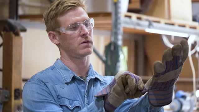 vídeos de stock e filmes b-roll de man standing in workshop putting on work gloves - one mid adult man only