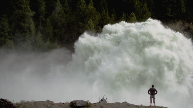 WS SLO MO Man standing  infont of huge wave exploding in river / Banks, Idaho, United States