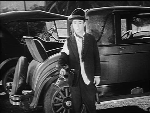 b/w 1926 man (harry langdon) standing near car getting knocked on head by head of hammer - 1926 stock videos & royalty-free footage