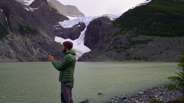 vídeos de stock, filmes e b-roll de homem parado perto do lago glaciar no parque nacional torres del paine - ponto de referência natural