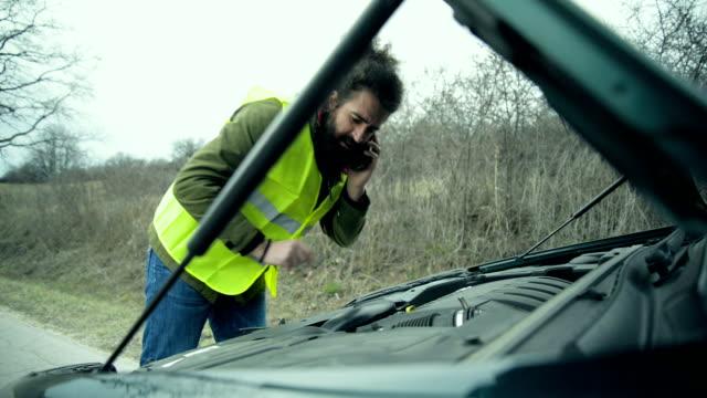 vídeos y material grabado en eventos de stock de hombre de pie junto al coche rota - grúa