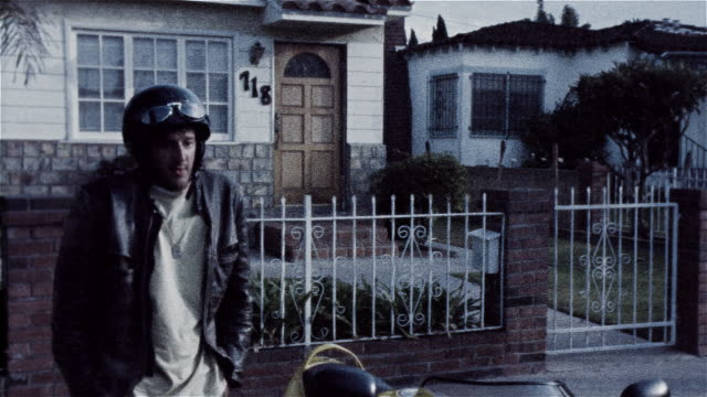stockvideo's en b-roll-footage met man standing next to motorcycle parked in front of house looking very nervous and uncomfortable - cross processen
