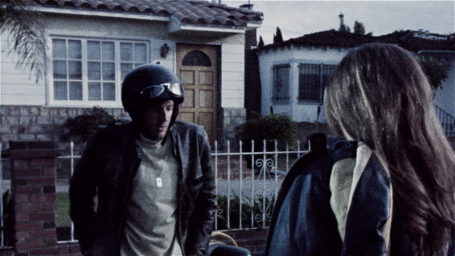 Man standing next to motorcycle sighing in front of woman / woman walking past him towards house