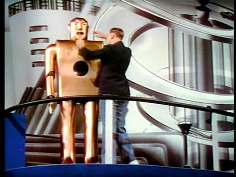 man standing next to robot + giving it cigarette / new york world's fair / industrial - esposizione universale di new york video stock e b–roll
