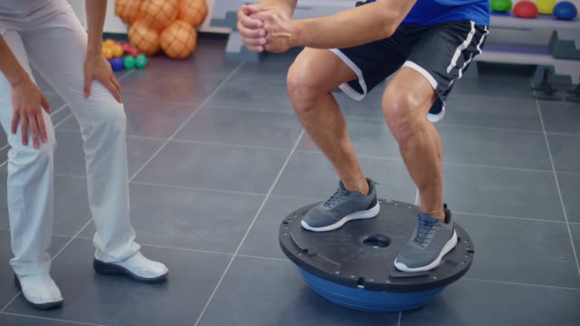 slo mo man standing on a balance ball supervised by his physical therapist - fitness ball stock videos & royalty-free footage