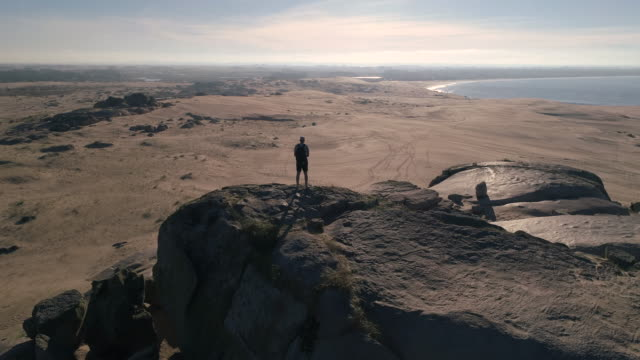 A man standing on a big rock between sand dunes at the beach