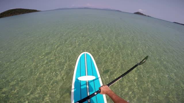 POV man die op een paddle board in tropische wateren