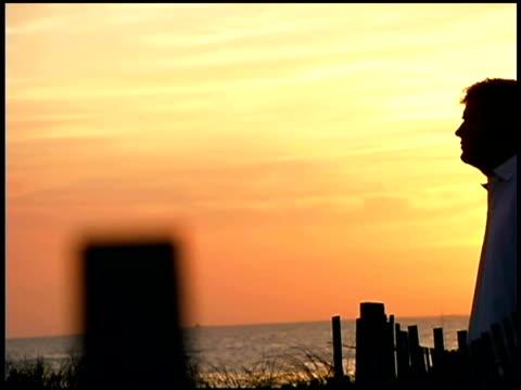 vidéos et rushes de man standing on beach at sunset - un seul homme d'âge moyen
