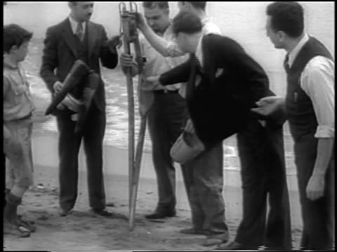B/W 1933 man standing on beach with remains of world's first liquidfueled rocket / newsreel