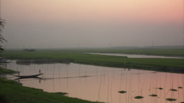 vídeos de stock, filmes e b-roll de ws, ha, man standing on boat, people walking on edge of water reservoir in background at sunset, bangladesh - bangladesh