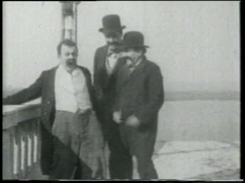 stockvideo's en b-roll-footage met b/w 1915 3 man standing on bridge upset about something jumping around / feature - 1915