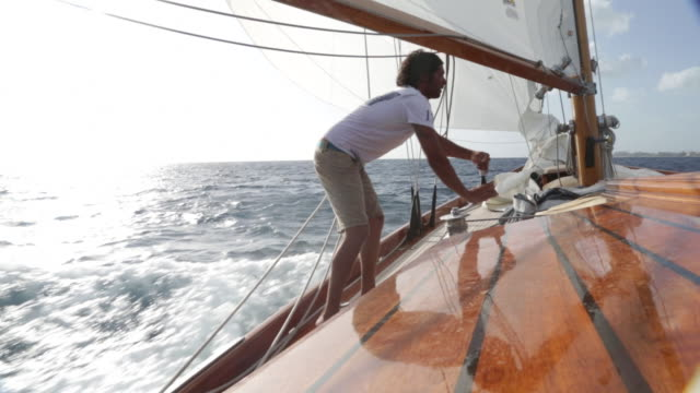 Man standing on deck of yacht turning winch as it sails quickly through the water.