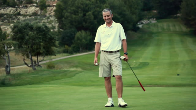 WS Man standing on golf course, practicing putt / Palma de Mallorca, Mallorca, Baleares, Spain