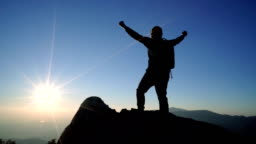 SLO MO Man standing on mountain and raising arms towards sunrise sky.