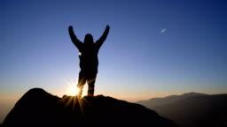 4K RT Man standing on mountain and raising arms towards sunrise sky.