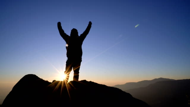4k rt man standing on mountain and raising arms towards sunrise sky. - reaching stock videos & royalty-free footage
