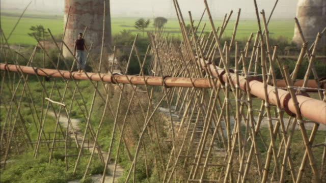vídeos de stock e filmes b-roll de ws, man standing on pipe supported by bamboo poles above ground, bangladesh - bambu material