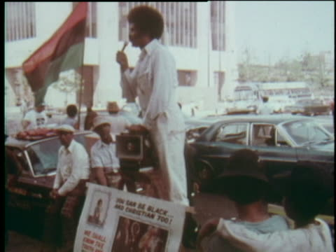 vidéos et rushes de man standing on platform speaking to crowd with microphone and speaker, sign below him - 'you can be black... and christian too!' - coiffure afro