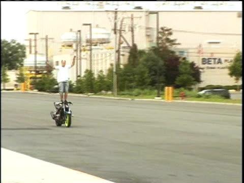 stockvideo's en b-roll-footage met ms, pan, man standing on riding motorcycle and doing wheelie on street, usa - hanenkam haardracht
