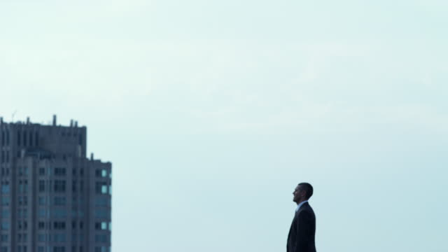 ws man standing on roof against sky, chicago, illinois, usa - 全套西裝 個影片檔及 b 捲影像