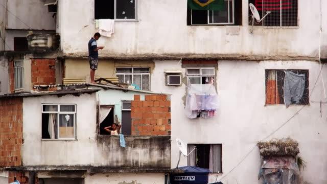 RIO DE JANEIRO, BRAZIL - JUNE 23: Man standing on roof and girl on balcony in Rio de Janeiro, 2013