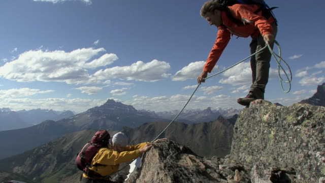 vidéos et rushes de ws, man standing on summit assisting female climber in ascending, banff national park, alberta, canada - corde