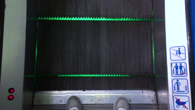 Man Standing on the Border on the Escalator when it's Moving Up