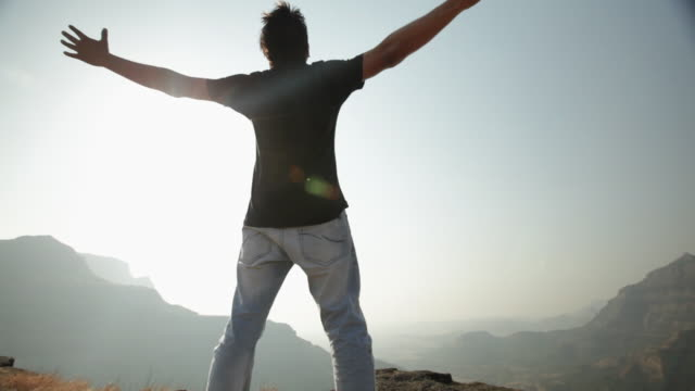 man standing on the cliff of mountain with his arms outstretched - ausgestreckte arme stock-videos und b-roll-filmmaterial