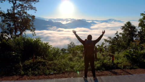 aerial man standing on the mountain and raising his hands in morning sunrise - on top of stock videos & royalty-free footage