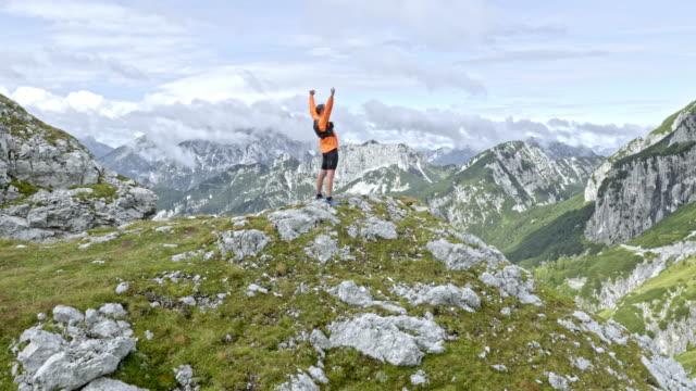 vidéos et rushes de aerial homme debout sur le sommet de la montagne et d'élever ses mains en l'air au-dessus de la magnifique vallée - bras en l'air