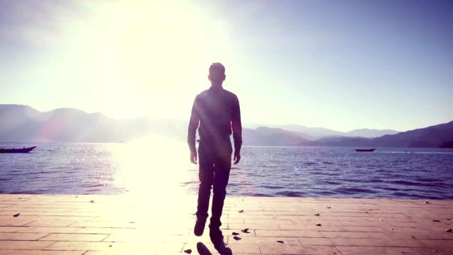 Mann steht am Ufer des Sees bei Sonnenaufgang