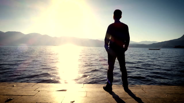 man standing on the shore of lake at sunset - the way forward stock videos & royalty-free footage