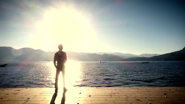Man standing on the shore of lake at sunset
